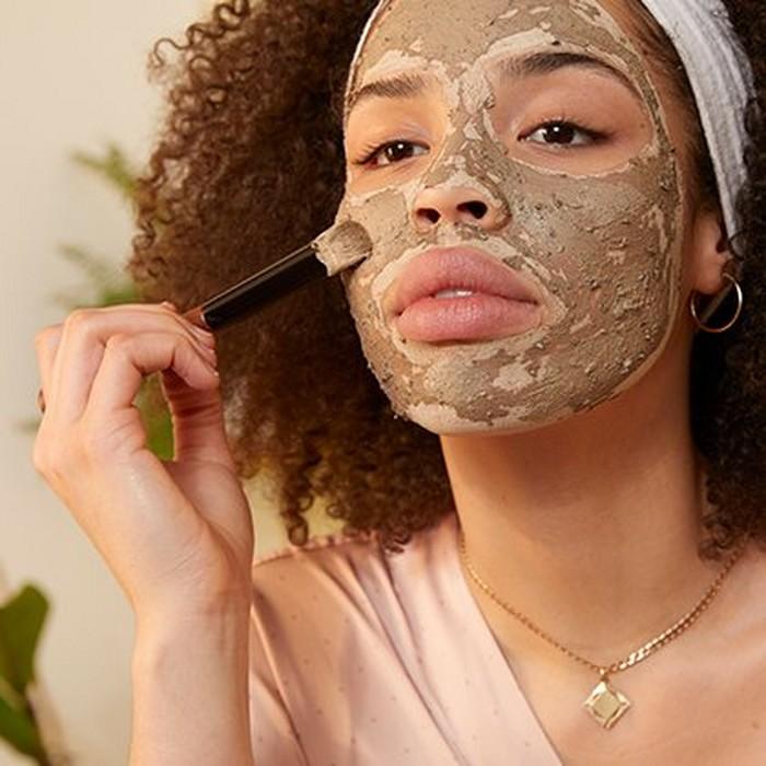 Frau beim Auftragen der Charcoal Gesichtsmaske mit einem Pinsel