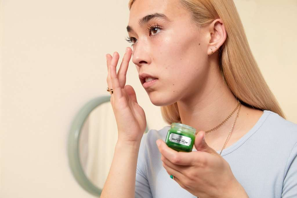 WOMAN PUTTING ON THE BODY SHOP DROPS OF YOUTH
