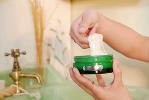 Hands scooping The Body Shop Drops of Youth Sleeping Mask