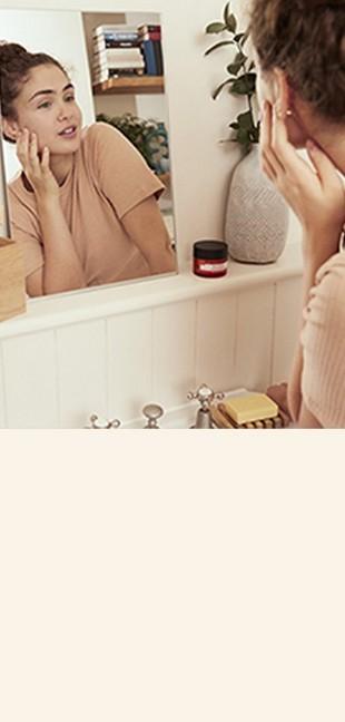 Model looking at skin in bathroom mirror