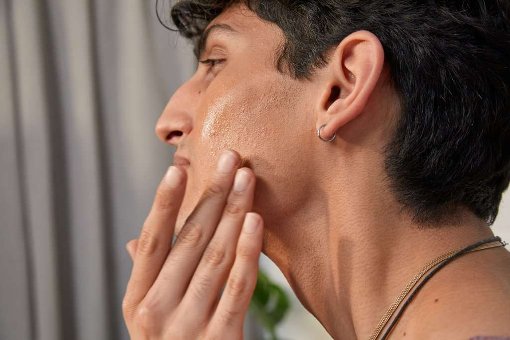 Man applying foundation to his face