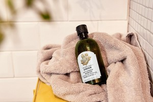 Bottle of The Body Shop Ginger Shampoo on a towel