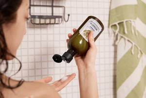 Woman applying The Body Shop Ginger Conditioner