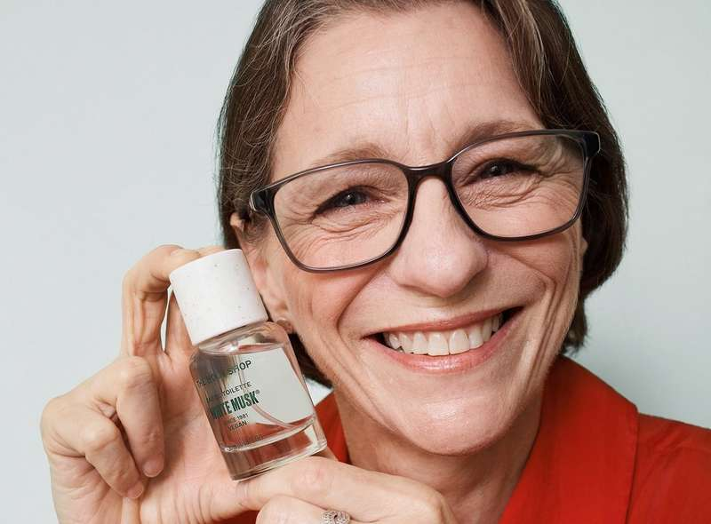 Karen, Independent Consultant, smiling with The Body Shop White Musk fragrance