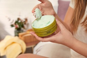 Woman scooping The Body Shop Hemp Body Butter from tub