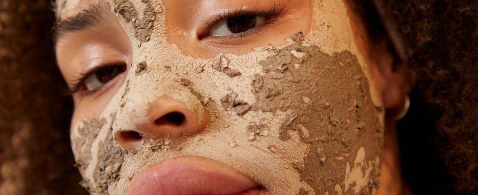 Rostro de una mujer cubierto de la mascarilla facial de carbón