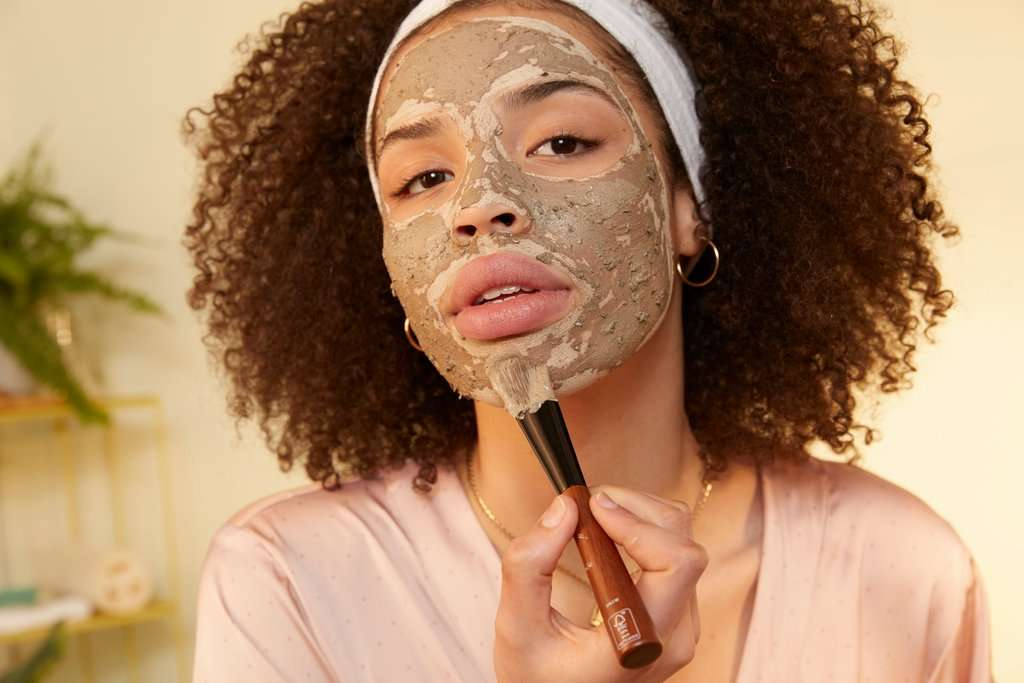 Woman applying charcoal face mask