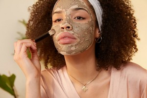 Woman applying The Body Shop Himalayan Charcoal mask
