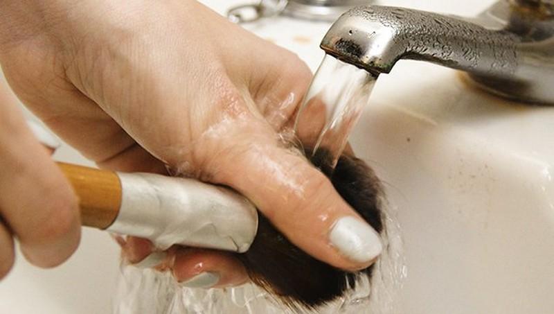 Una mano lavando una brocha de maquillaje