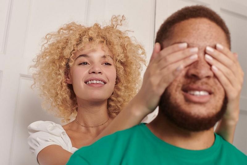 Mujer tapándole los ojos a un hombre