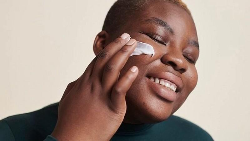 Woman applying face moisturiser