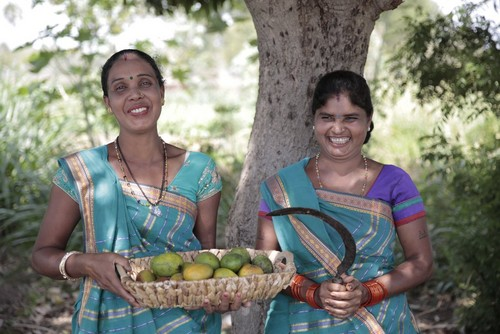 Women holding basket of mangoes
