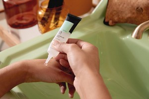 Hands applying mattfying lotion