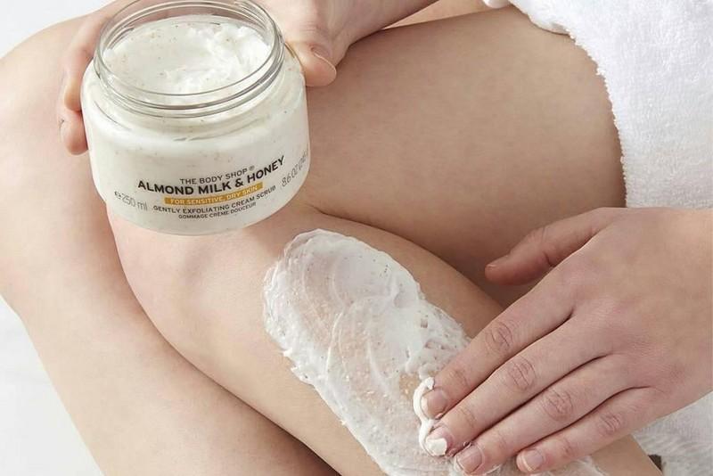 Frau, die Almond Milk & Honey Scrub auf ihre Beine reibt