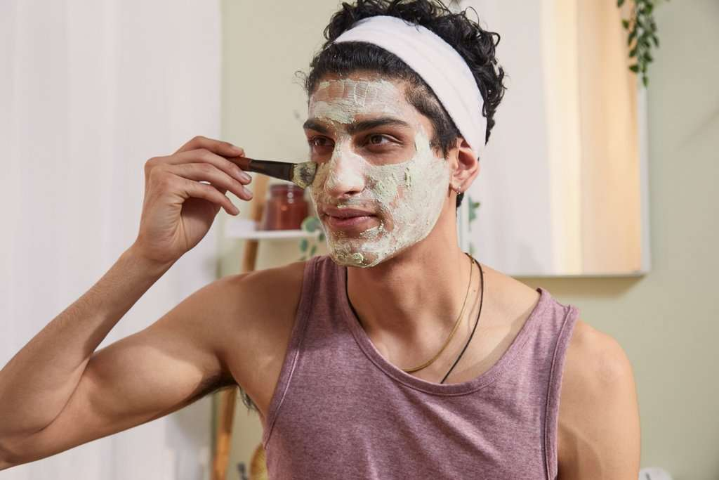 Man applying pollution clearing mask