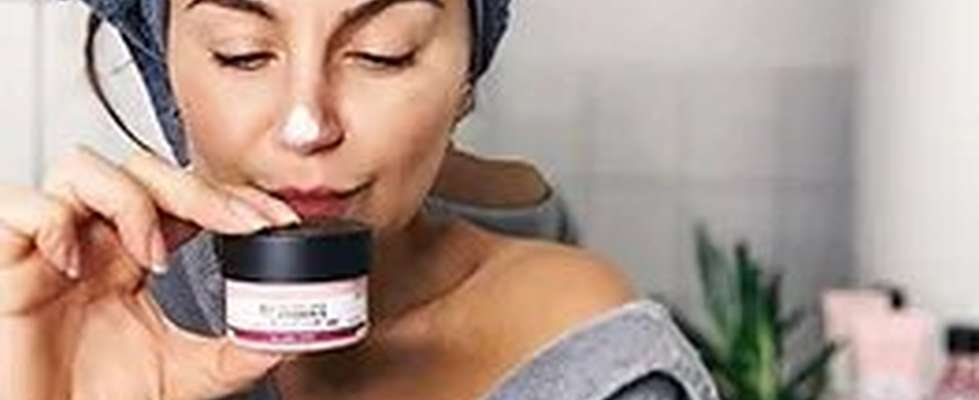WOMEN HOLDING POT OF BODYSHOP VITAMIN E MOISTURE CREAM