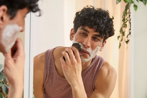 A man looking into a mirror and shaving
