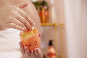 Main prenant une part de yogourt corporel à mangue de The Body Shop