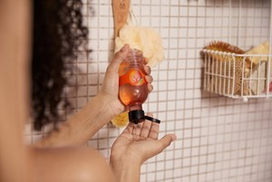 Hands squeezing The Body Shop Mango Shower Gel