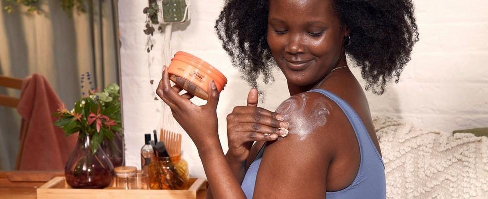 一位正在肩膀塗抹身體潤膚霜的女性