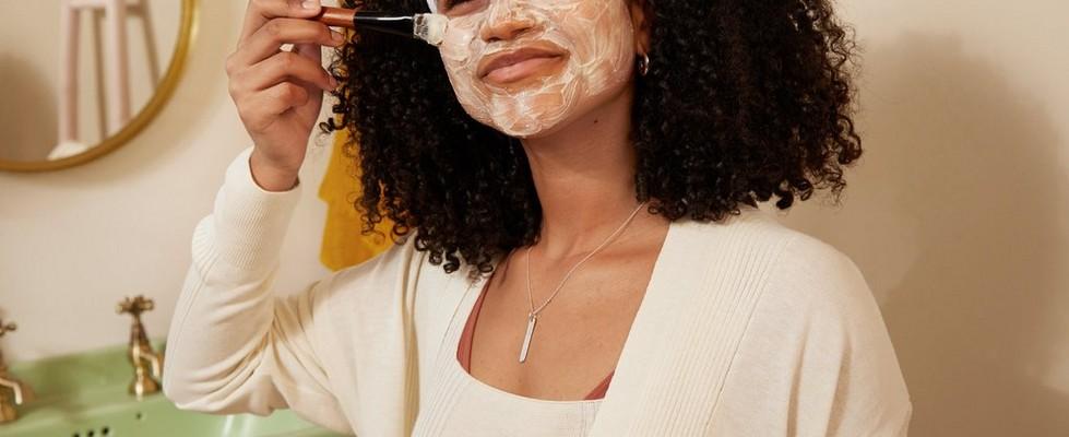 Une femme appliquant un masque facial apaisant