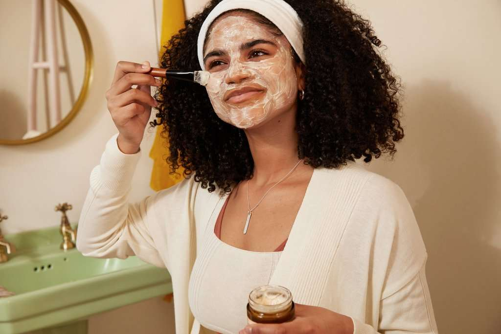 Woman applying soothing face mask