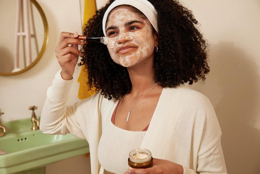 Frau beim Auftragen einer beruhigenden Gesichtsmaske