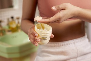Hand entnimmt Moringa Body Yogurt von The Body Shop