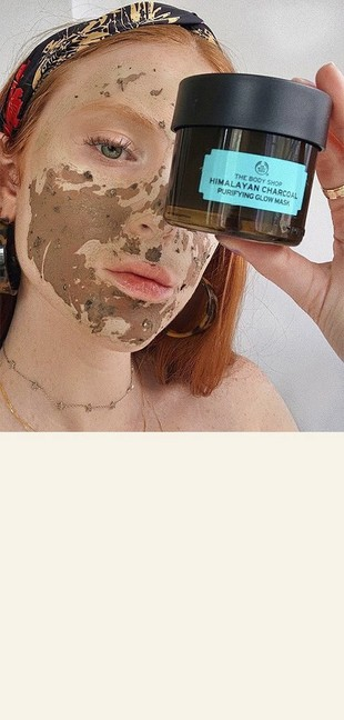 Woman holding charcoal mask next to face