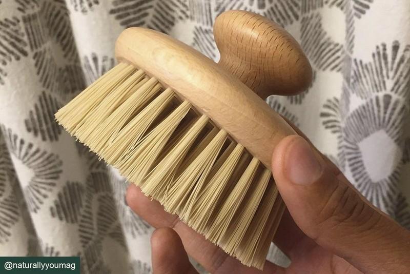 Persona sosteniendo un cepillo corporal redondo