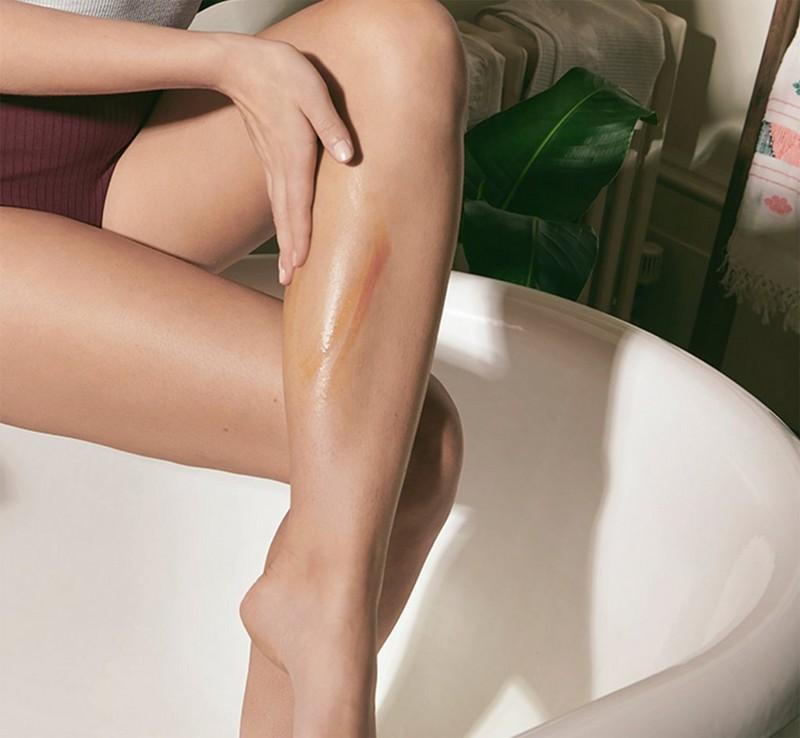 Model applying fake tan to legs