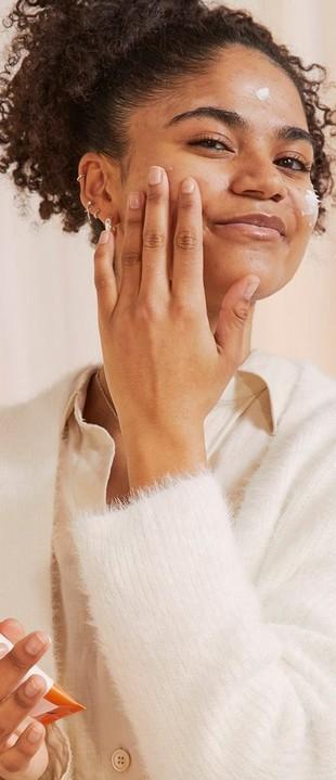 Mujer aplicando hidratante con FPS en el rostro