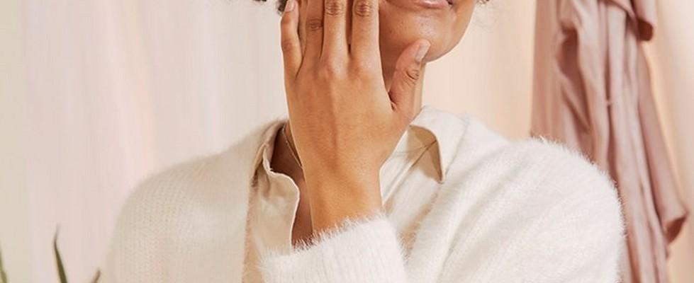 Woman applying The Body Shop Vitamin C skincare product
