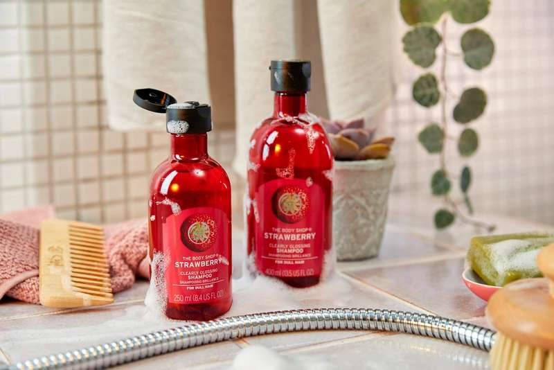 Two strawberry haircare products in a bathroom