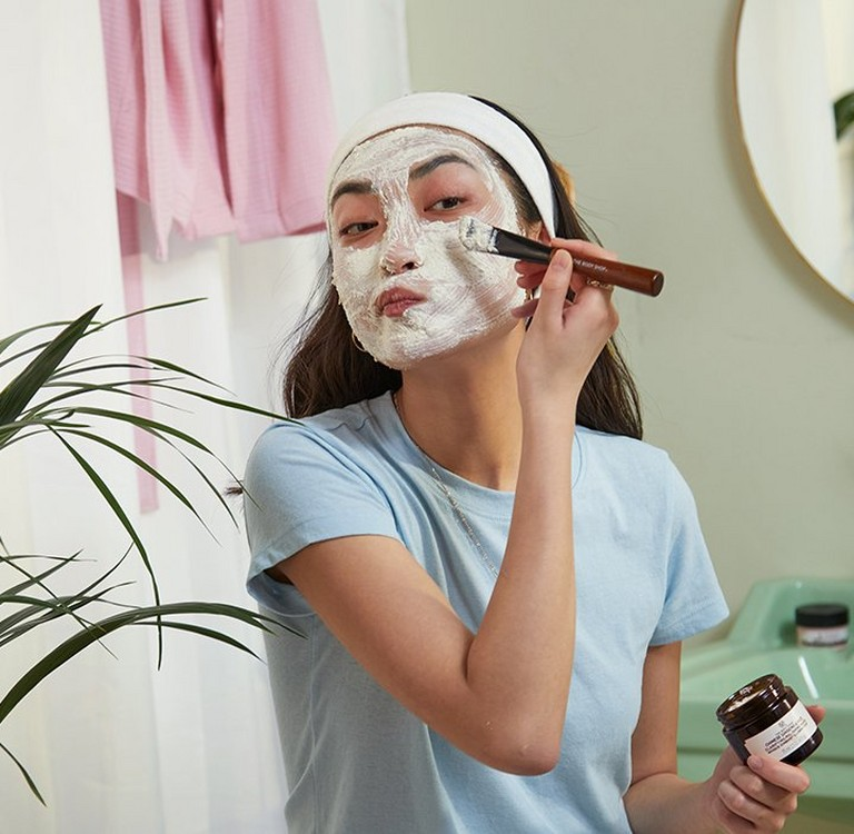 Woman applying face mask with a brush in the bathroom