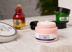 Selection of The Body Shop skincare products on white tiled bathroom surface