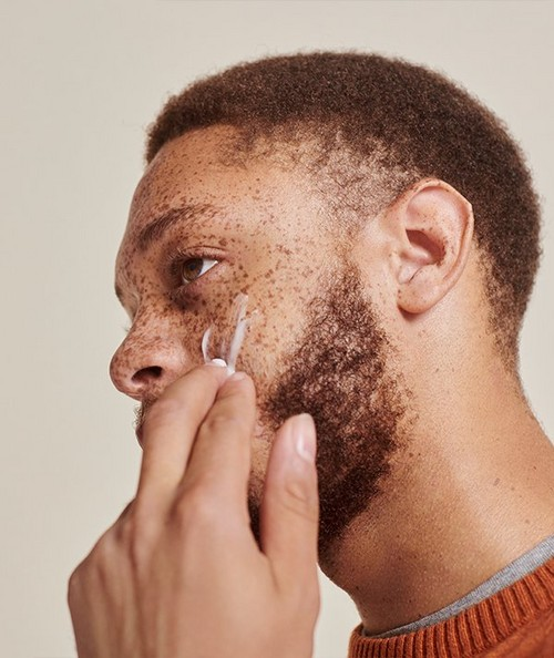 Male model applying skincare product to face