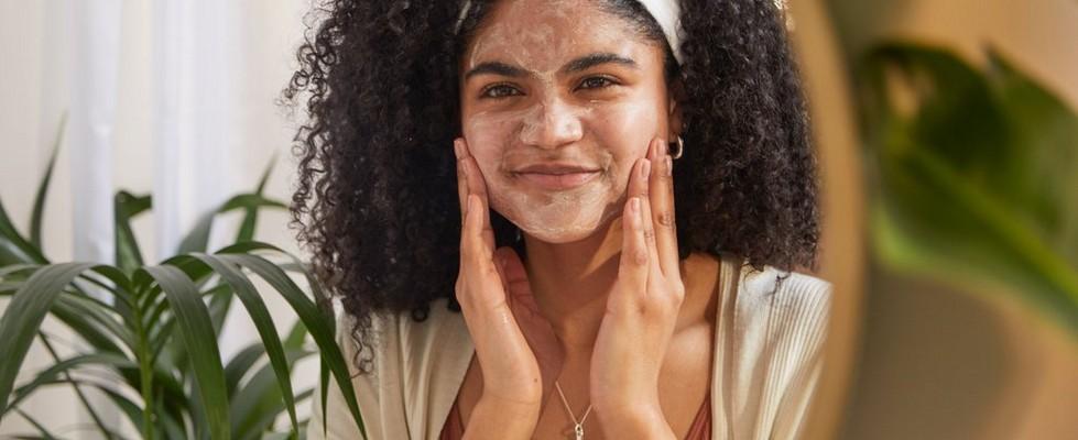 Una mujer se aplica una mascarilla exfoliante en el rostro