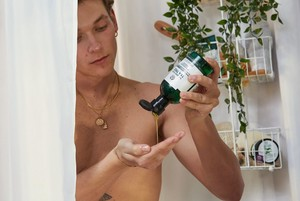 Man using The Body Shop Tea Tree Body Wash in the shower
