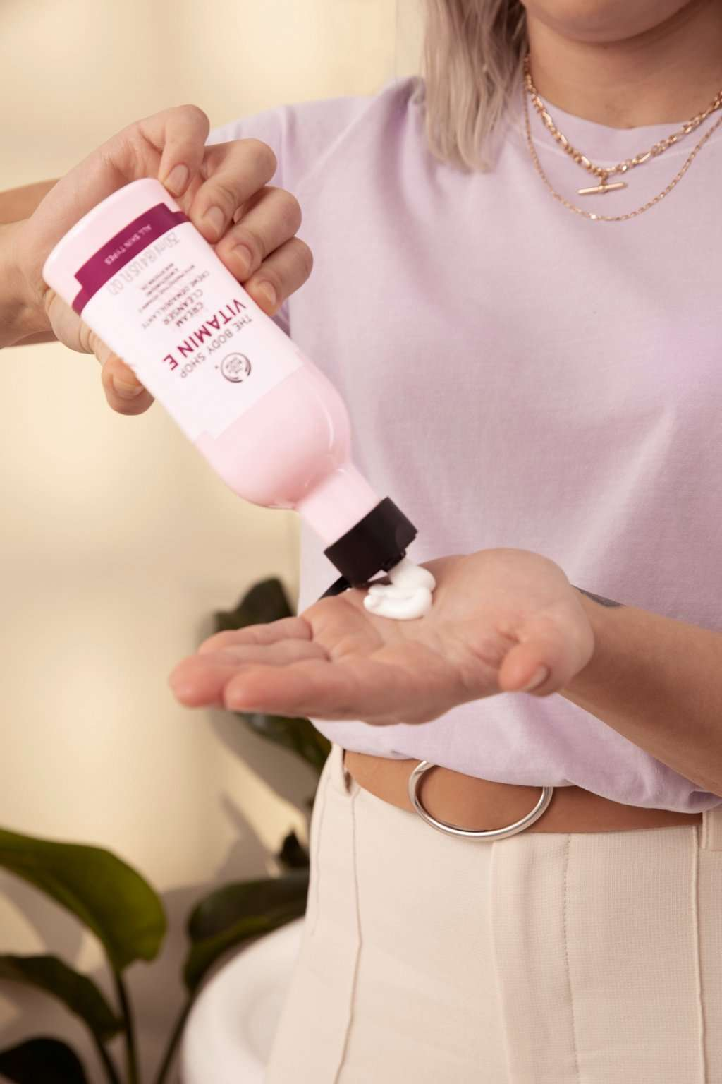 Une femme versant de la crème nettoyante d'une bouteille