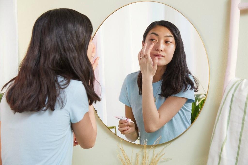 Une femme applique une crème sur son visage