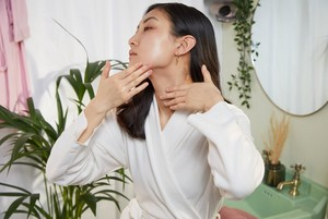 Woman applying serum on her neck