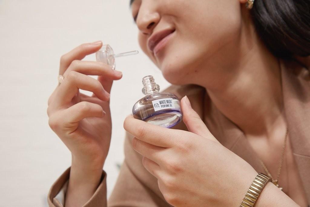 Une femme humant l'huile de parfum White Musk de The Body Shop