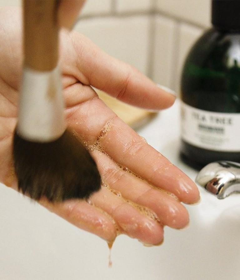 Una persona limpia una brocha ayudándose de su mano
