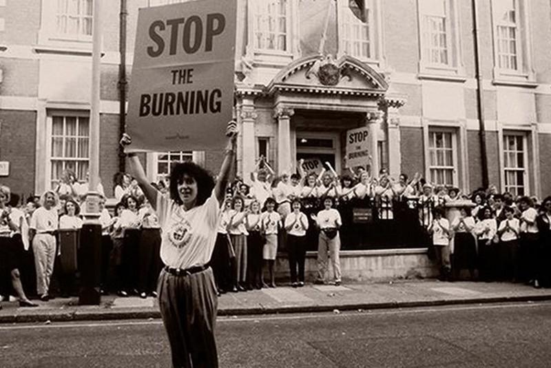"Anita Roddick holding a ""Stop the burning"" sign"