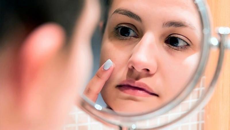 Frau, die sich im Spiegel betrachtet